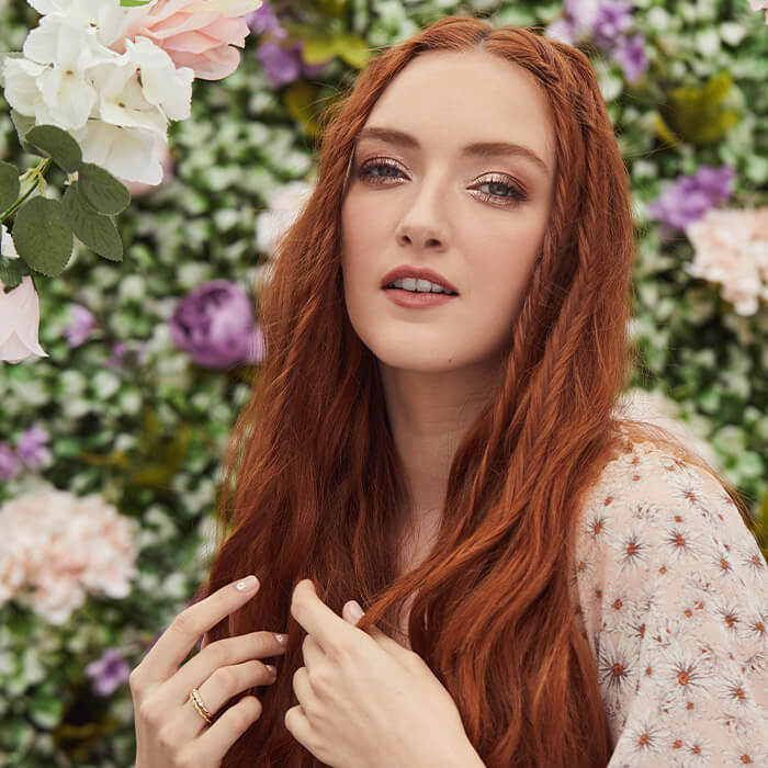 Close-up image of a model with copper hair in a floral outfit and wearing rose gold eyeshadow makeup against a garden background