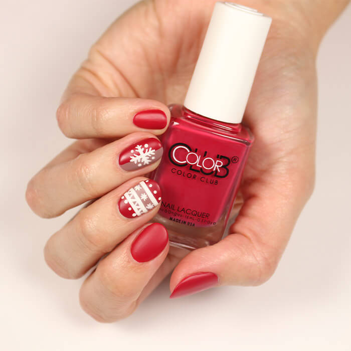 Image of a model's hand with holiday themed nail art mani holding the COLOR CLUB Nail Polish in Regatta Red