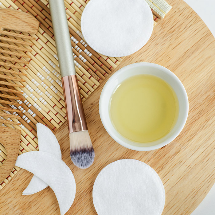 A photo of a small white bowl with cosmetic olive oil, cotton pads, make-up brush and wooden hair brush