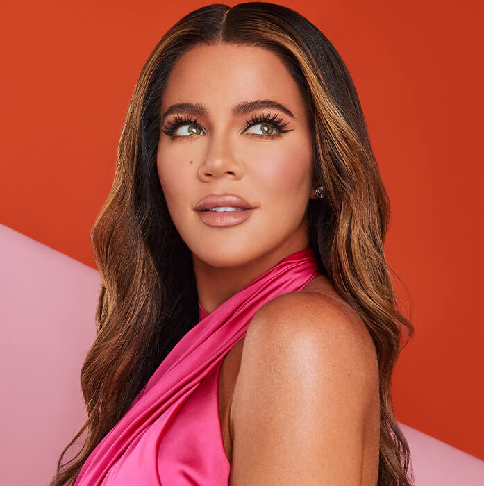 Khloé Kardashian in a pink dress posing against pink and red background