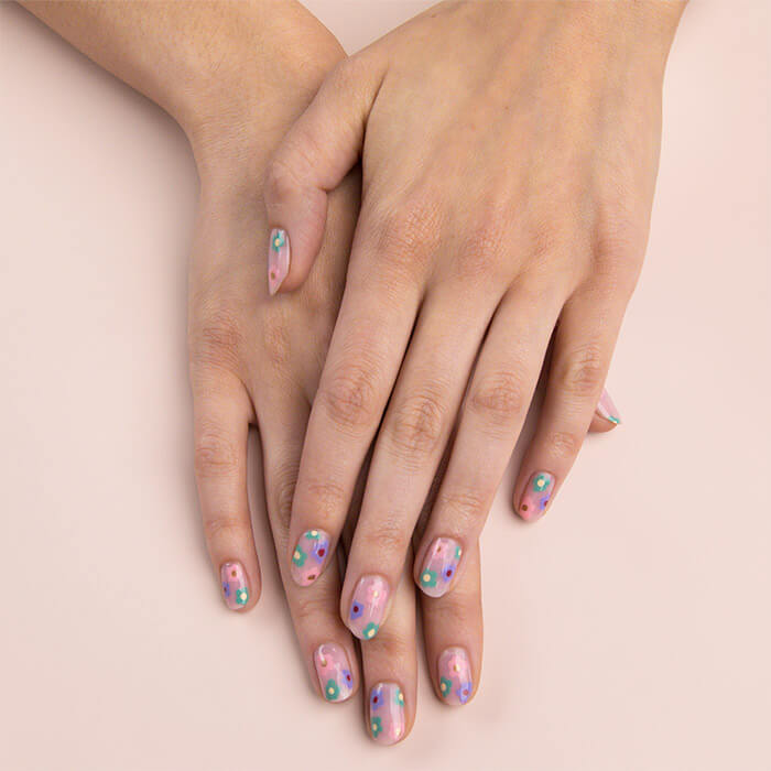 Close-up image of a model's hands with colorful flower nail art on top of each other