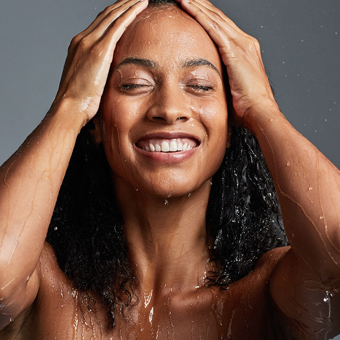 An image of a woman washing her hair against a grey background