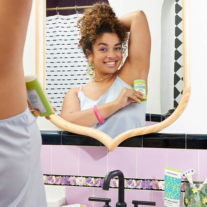 Image of a model applying REFRESHMENTS Breezy Deodorant in Eucalyptus Julep on her underarm while smiling in front of her bathroom mirror