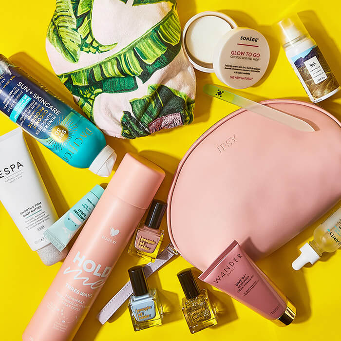 Image of skincare, nail, makeup, hair care products, and IPSY makeup pouches on yellow background