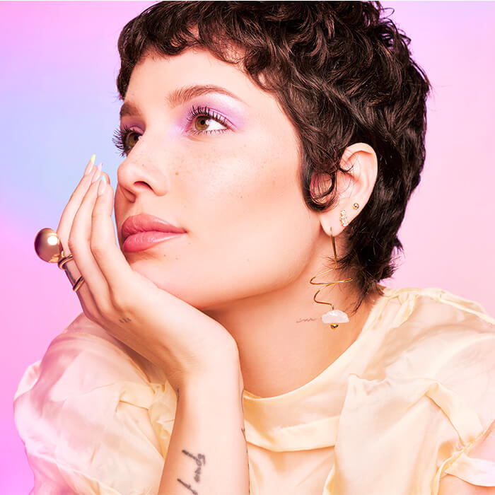 Side profile image of Halsey looking chic and posing against colorful background