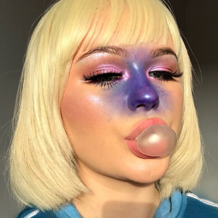 Close-up of a woman with blonde hair rocking a bold, shimmery pink and purple eye makeup look while blowing bubblegum