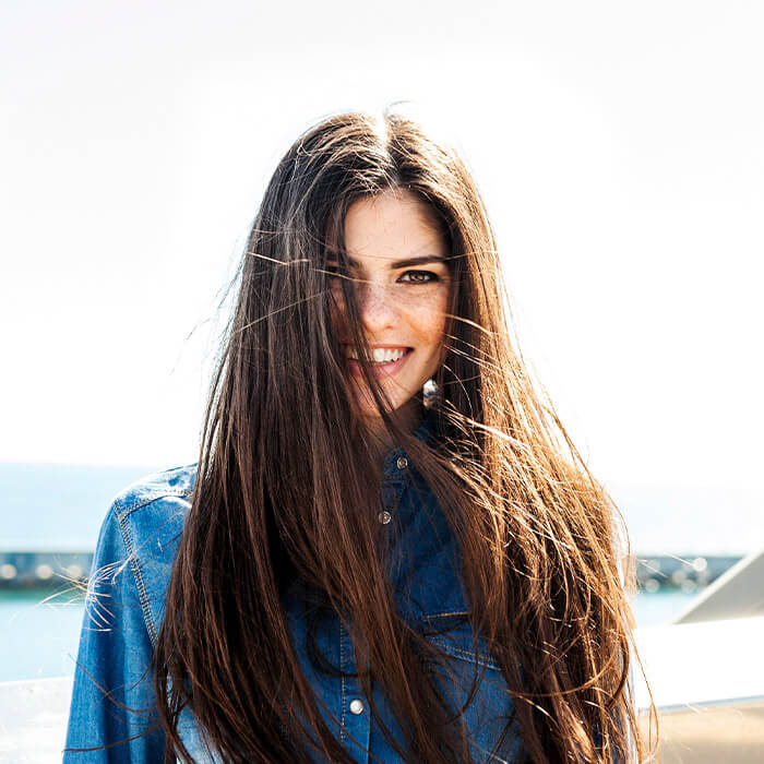 Woman with long hair wearing denim and smiling with harbor view as background