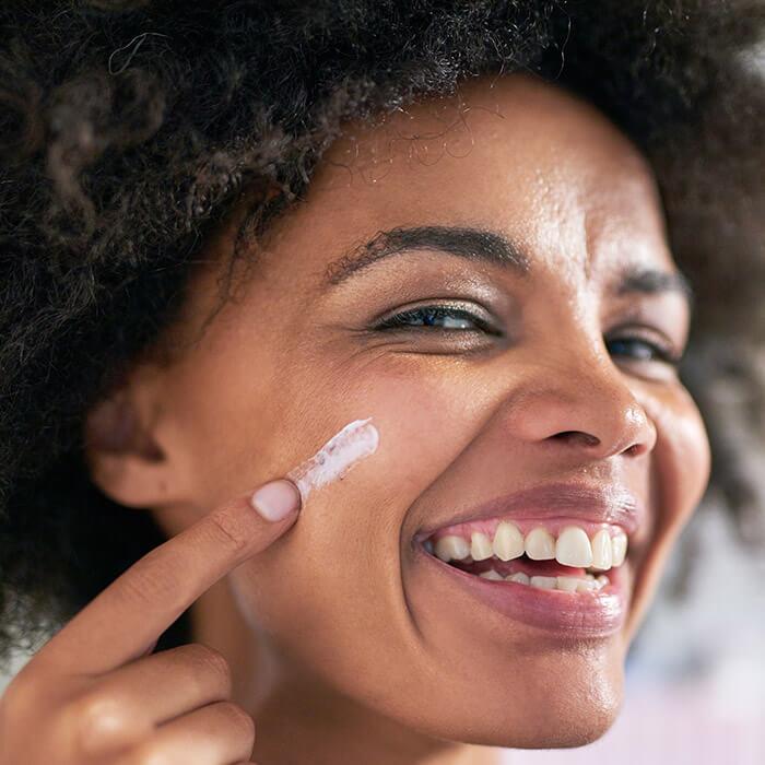 Black woman applying face cream on her cheek