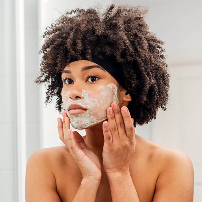 Young woman applying mask on her face while looking at herself in the bathroom mirror