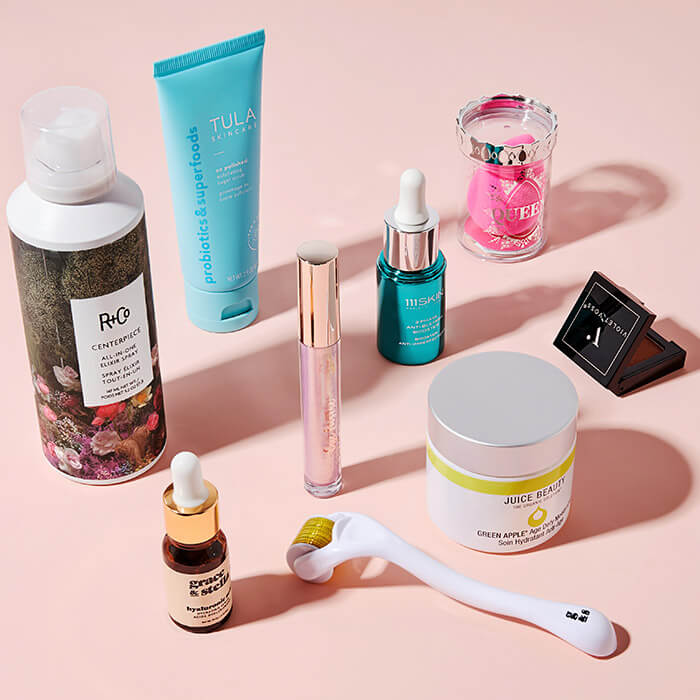 Flat lay image of hair care, makeup, and skincare products and tools on pink background