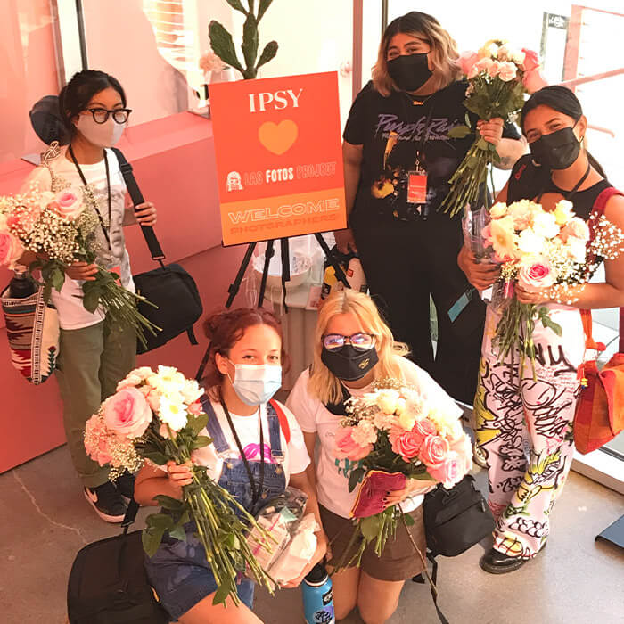 """Photo of a group of female photographers with their face masks on each holding a bouquet of flowers around a sign that says """"IPSY Las Fotos Project Welcome Photographers"""""""