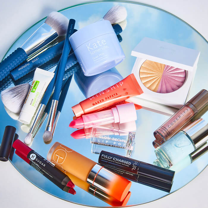 Image of nail, makeup, and skincare products and tools on a round mirror with a reflection of the sky