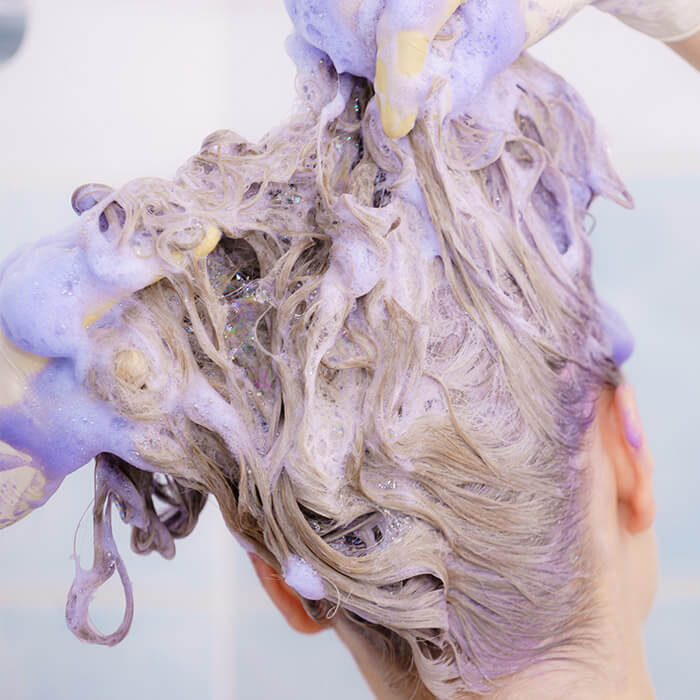Close-up of a woman with blonde hair applying toner to her hair