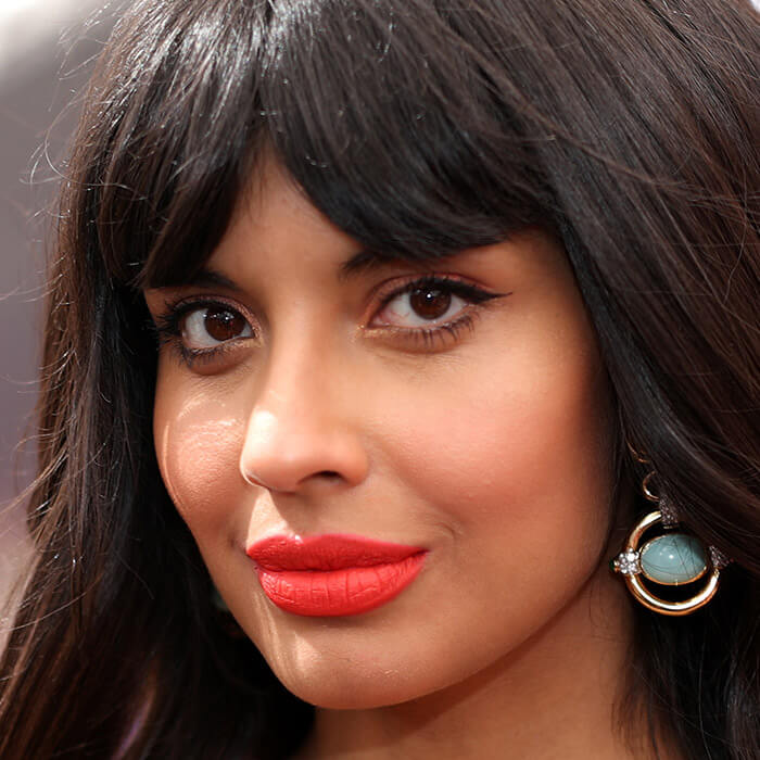 Jameela Jamil rocking a neutral makeup look paired with bright red lipstick