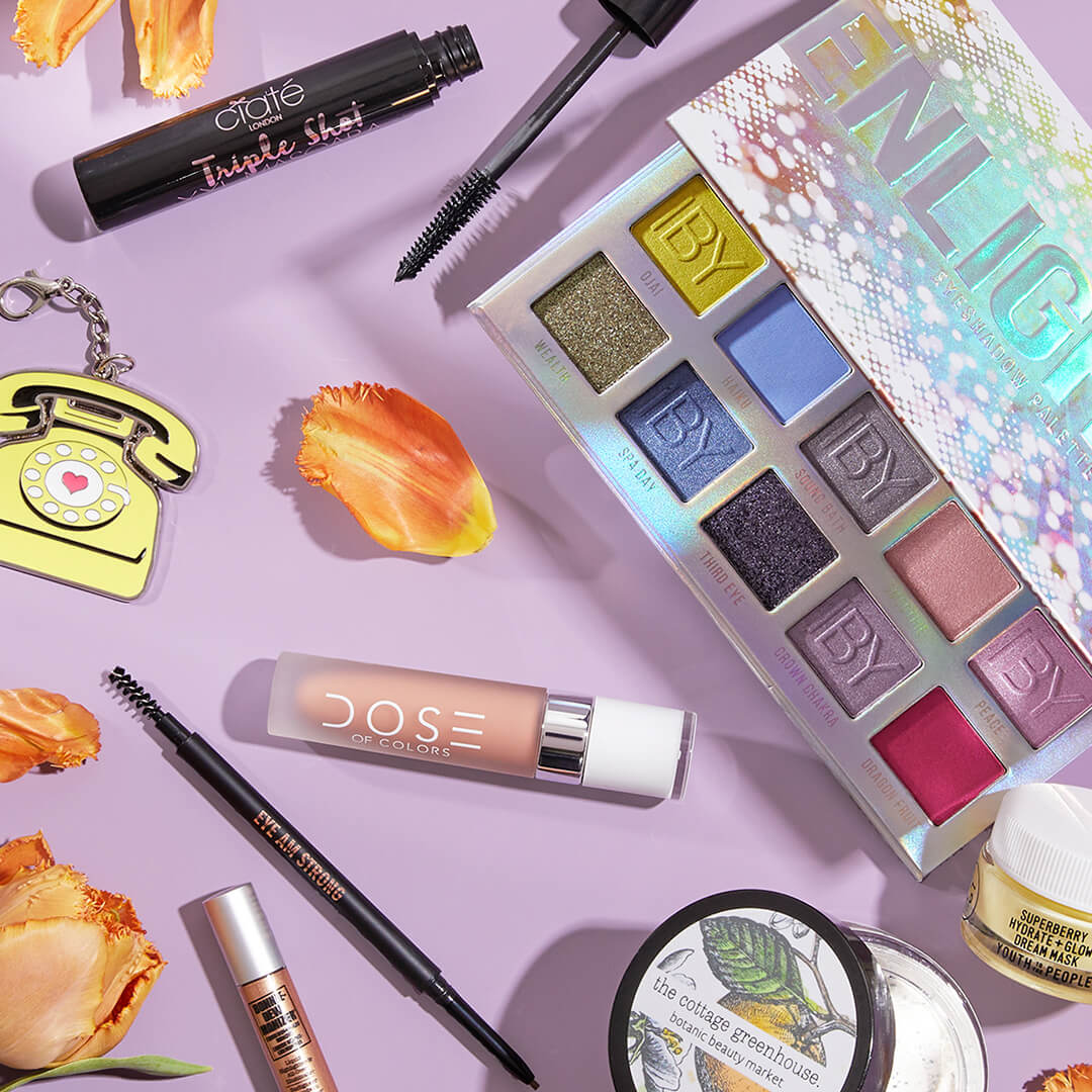 Flat lay image of different makeup and skincare products from various brands and orange flower petals on a violet surface