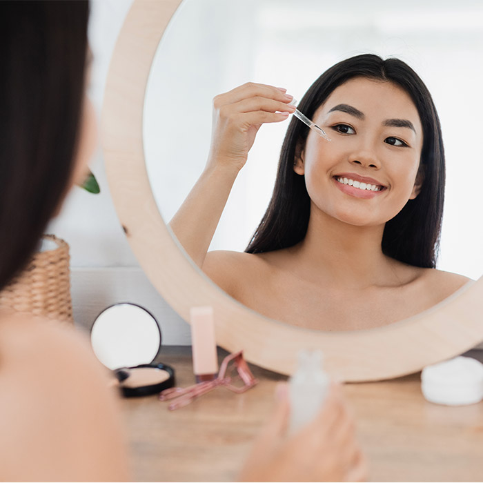 A photo of a woman facing the mirror and applying face serum