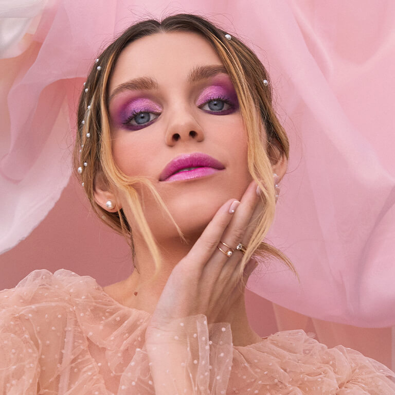 An image of a model wearing bold purple eyeshadow paired with glossy pink lipstick holding her jaw with one hand