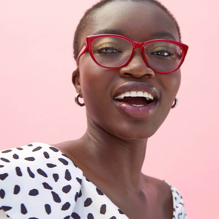 Close-up image of a smiling model wearing red eyeglasses and black and white pattern outfit against pink background