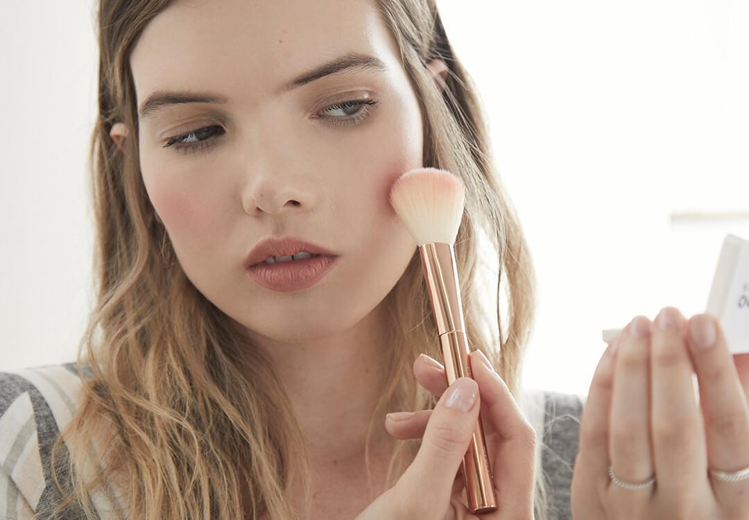 An image of a model applying blush makeup with a rose gold makeup brush