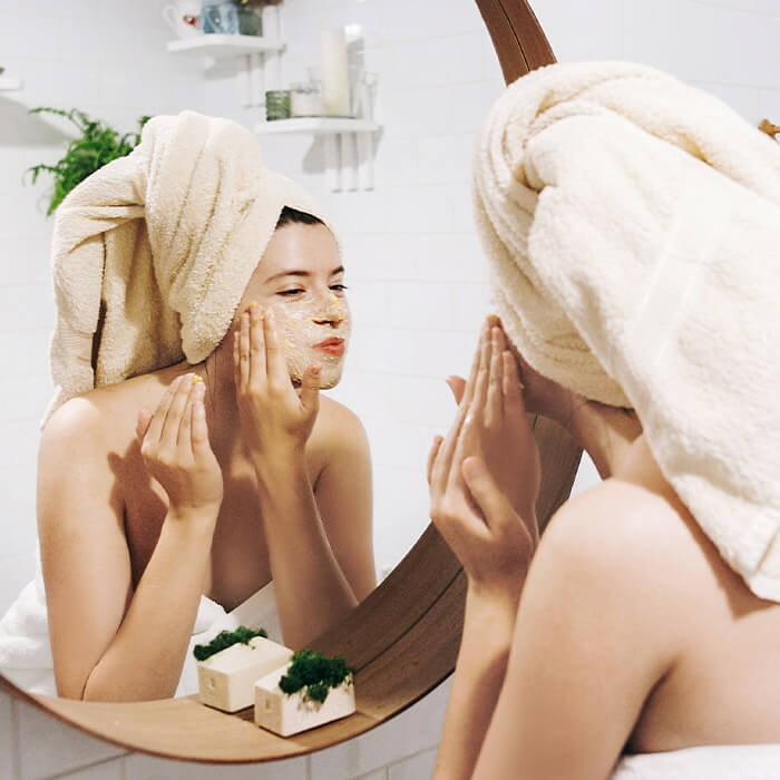Woman in a towel scrubbing her face while looking in the mirror of her bathroom