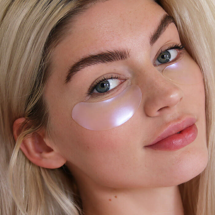 Close-up image of a model wearing TULA Eye Feel Amazing Cooling & Brightening Hydrogel Eye Masks