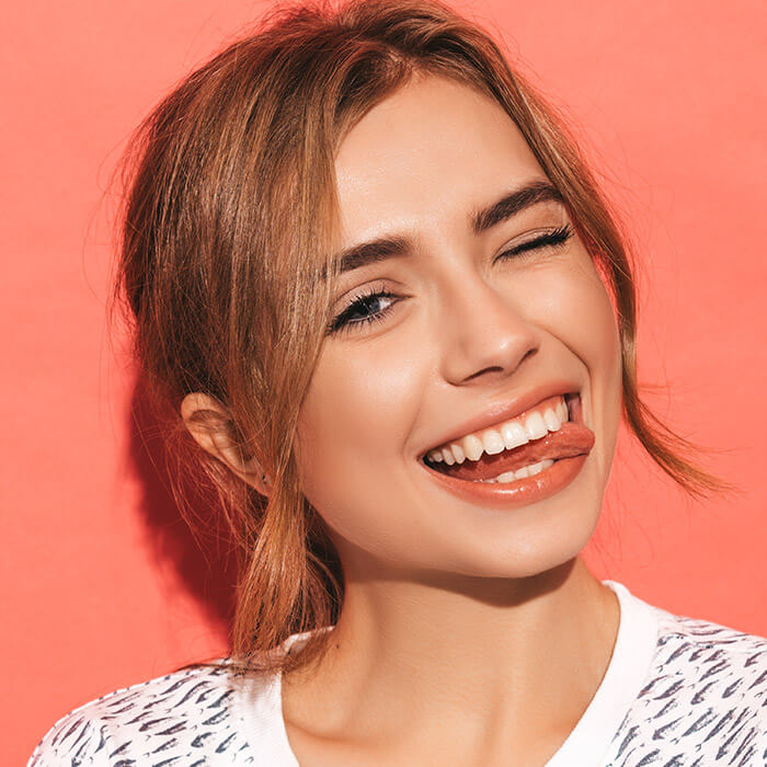 Close-up of a girl in a fish-patterned shirt smiling with tongue out