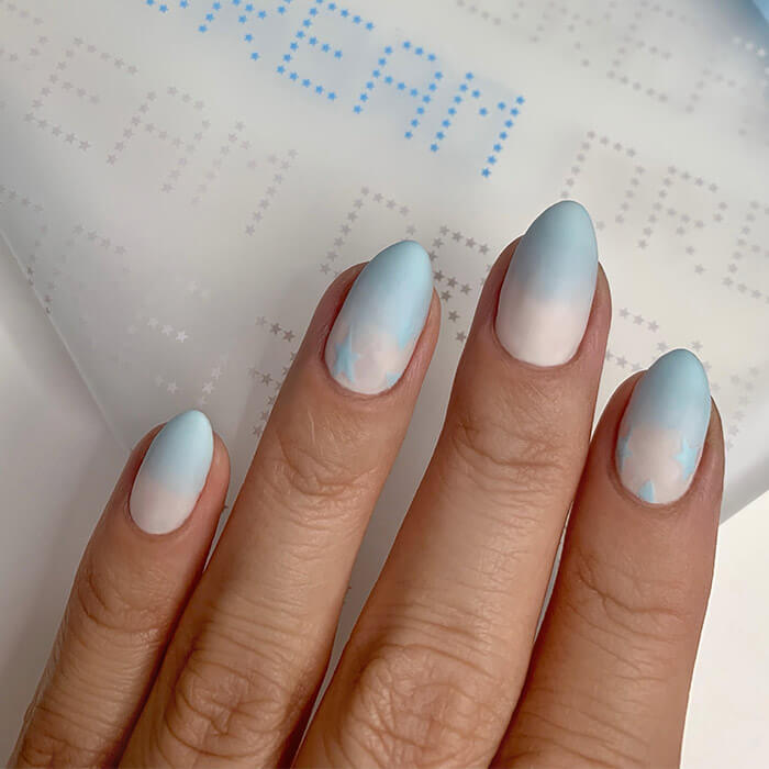 Close-up of a model's nails with blue and white ombre nail art touching the January 2021 IPSY Glam Bag
