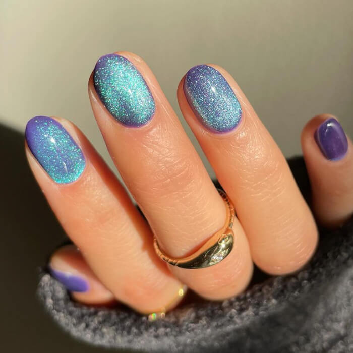 Close-up of a woman's nails with aquamarine and purple velvet nail art
