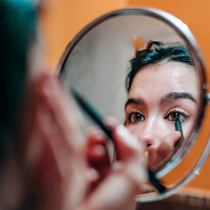 A photo of a woman applying eyeliner
