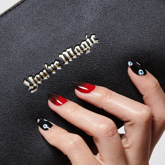 Close-up image of a model's hand with red and black nail art mani holding the IPSY October Glam Bag