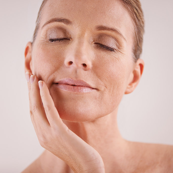 A photo of a mature woman touching her face