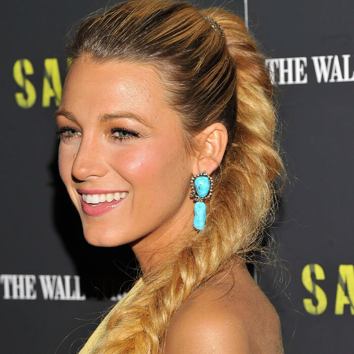 Close-up of Blake Lively rocking fishtail braids, a no-makeup makeup look, and turquoise dangling earrings on the red carpet