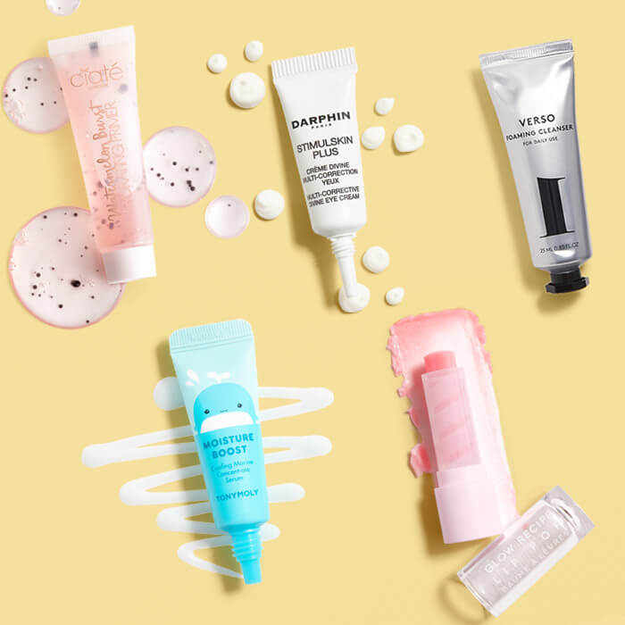 Beauty products from various brands swatched on yellow background