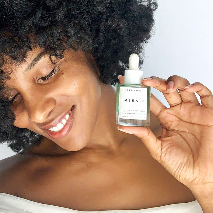 Close-up of a Black woman holding the HERBIVORE Emerald Deep Moisture Glow Oil