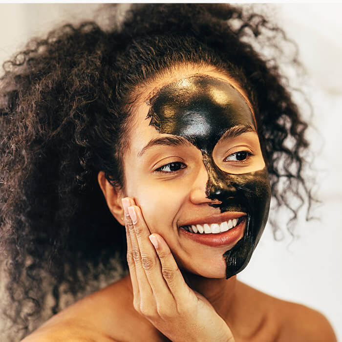 Smiling woman with charcoal mask on her face
