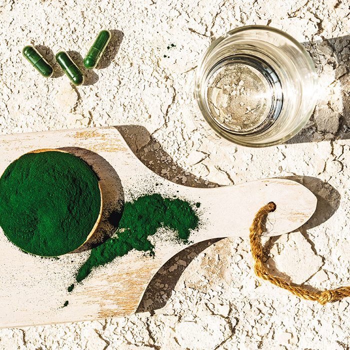 A photo of green algae powder in pills and capsules with a glass
