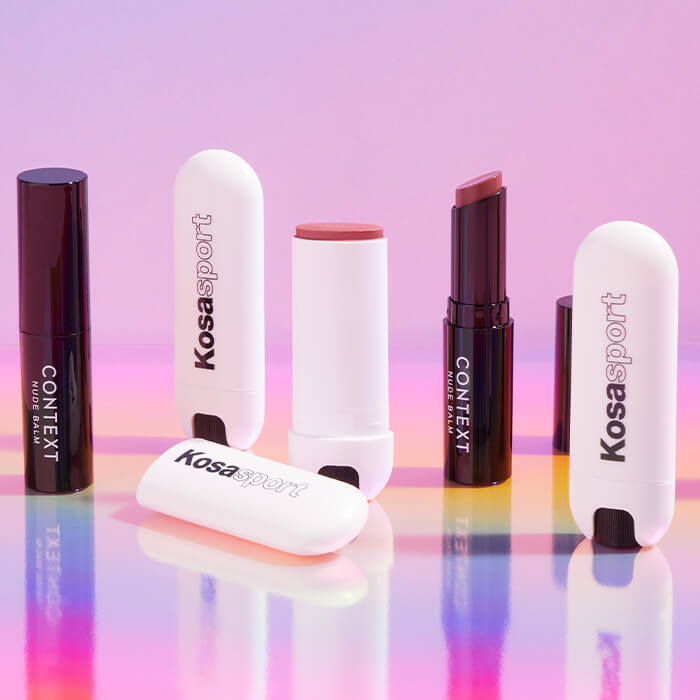 Tubes of BEAUTY FOR REAL Lip Revival Tinted Lip Balm in Hannah and KOSAS Kosasport LipFuel Hyaluronic Lip Balm in Rush against colorful background