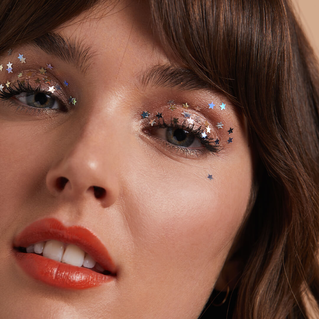 Close-up image of a model rocking a shimmery eyeshadow with star sequins