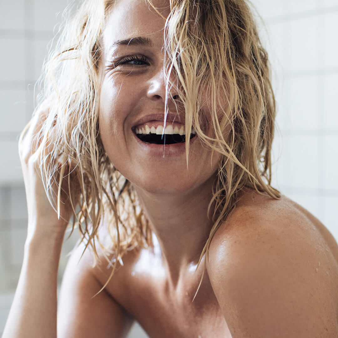 An image of a model rinsing her hair with apple cider vinegar.
