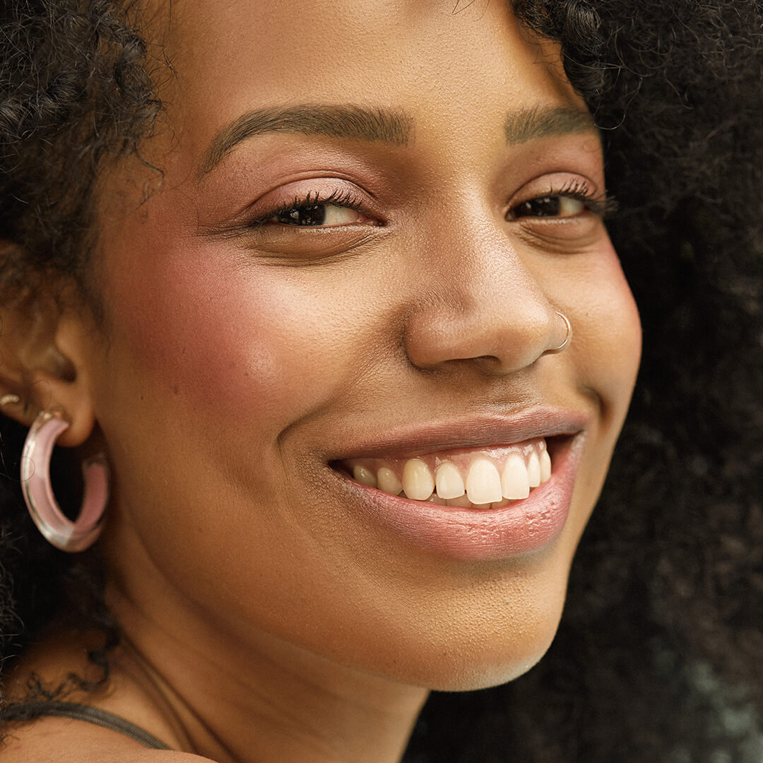 A close-up image of a model wearing rose gold eyeshadow and hoop earrings smiling big