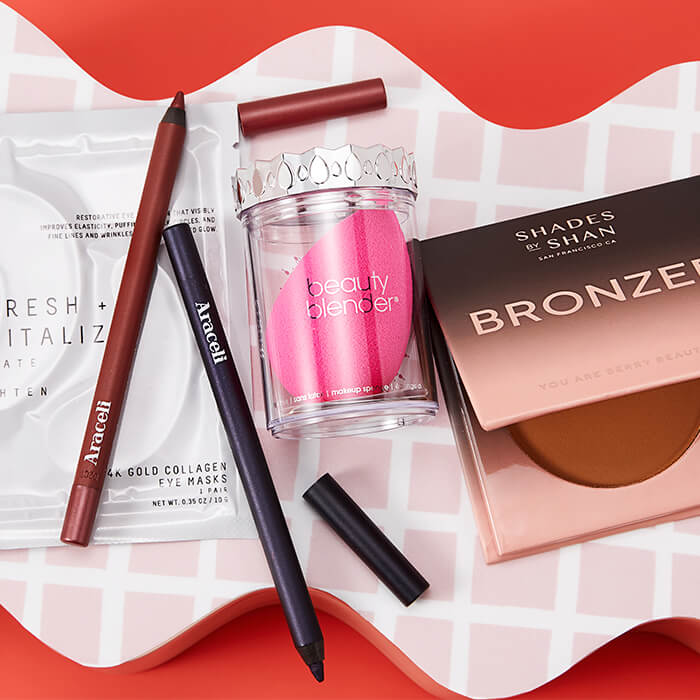 Flat-lay image of makeup and skincare products and tools from Latinx-led brands on pink tiles wavy block and orange background