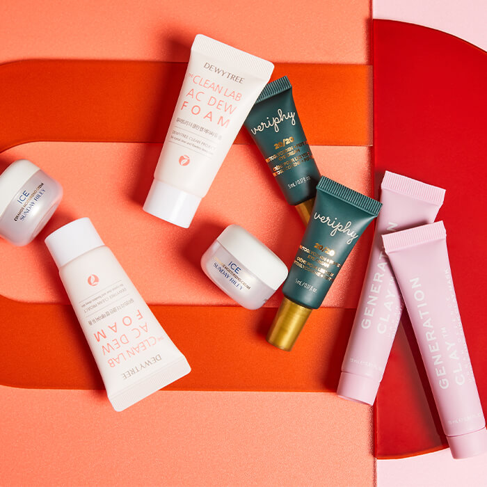 Flat lay image of skincare products from various brands on colorful pink, orange, and red background