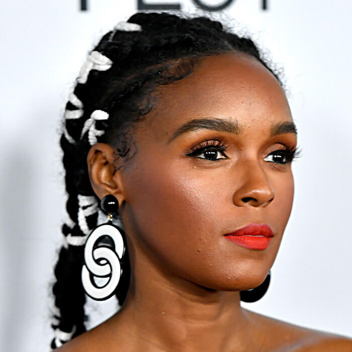 Janelle Monae rocking a braided updo hairstyle pairing it with a neutral eye makeup and bright red lips