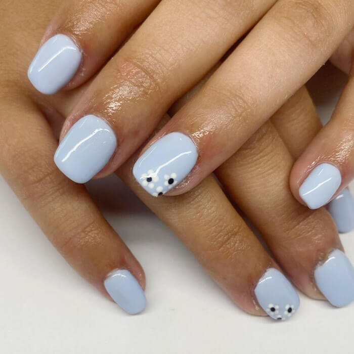 Woman's hands with light blue nail polish and white flowers accent nail art