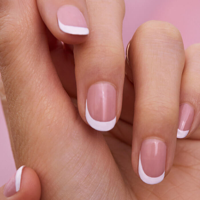 Close-up of model's hand with French tip mani