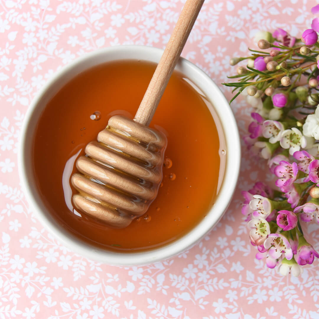 Image of a bowl of honey, honey dipper, and pink and white flowers on a pink floral background