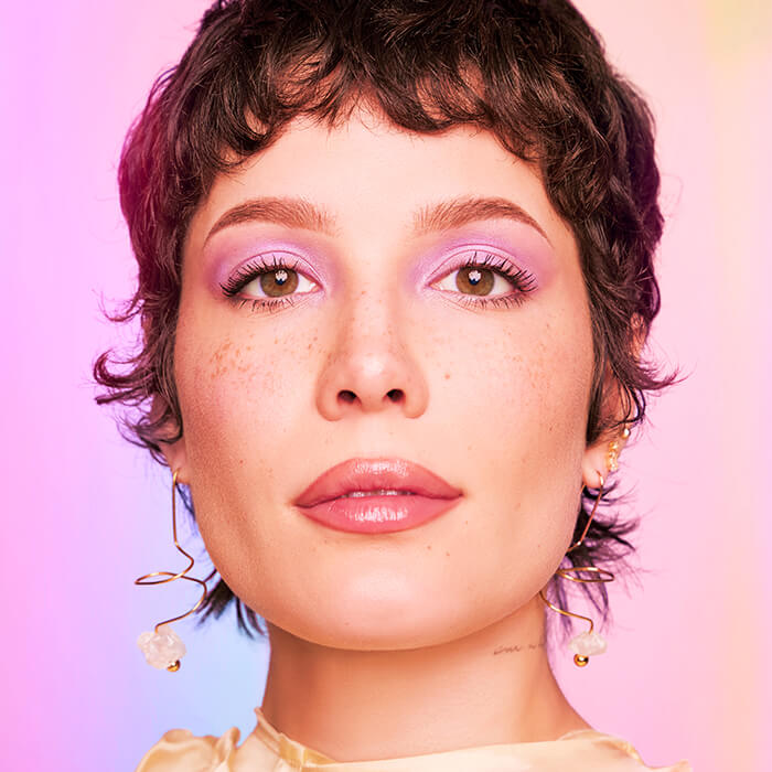 Close-up of Halsey rocking pink eyeshadow and mauve lips against colorful pastel background