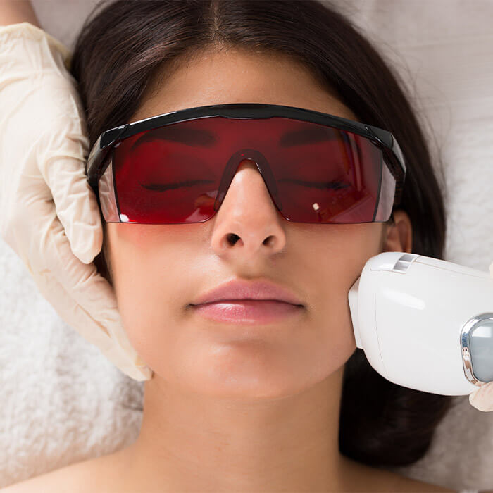 Woman wearing protective glasses getting a laser treatment