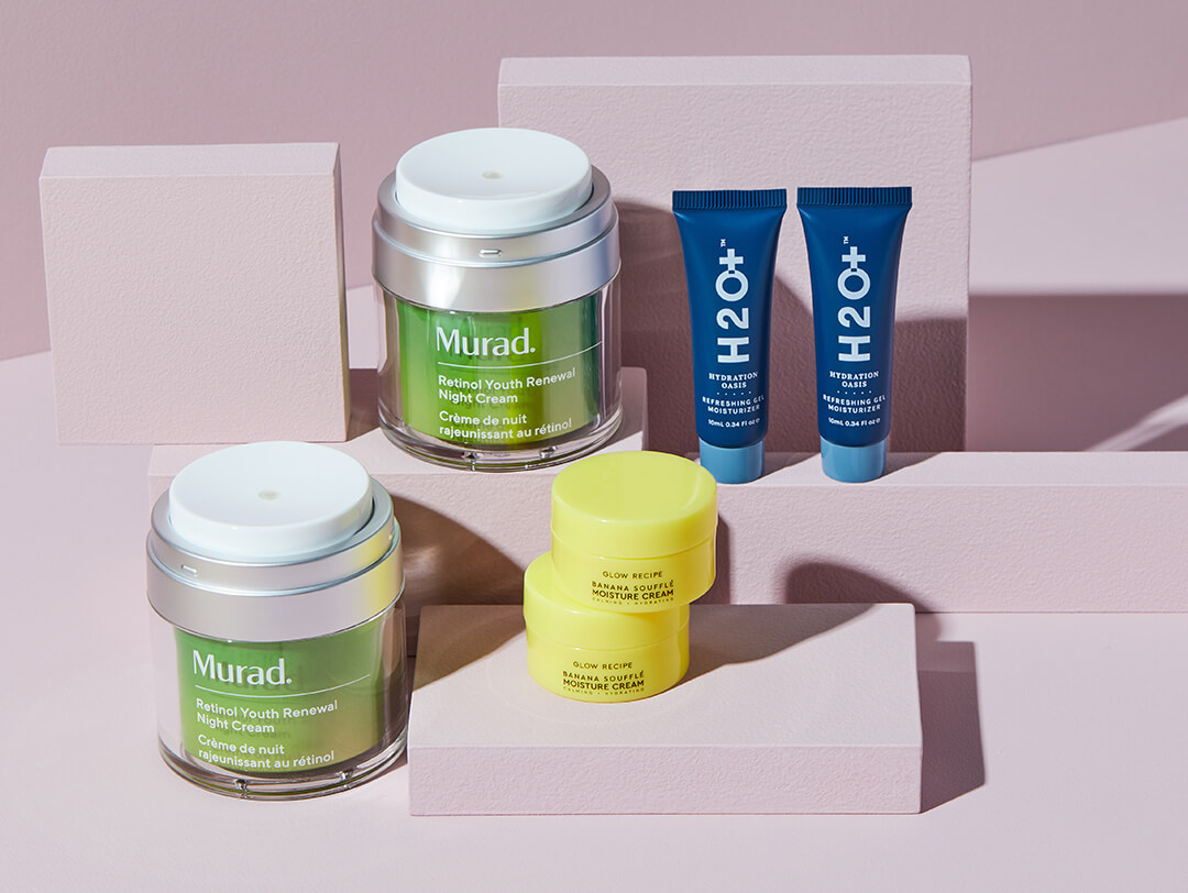 Flat lay image of GLOW RECIPE Banana Souffle Moisturizer, MURAD Retinol Night Cream, and H2o+ Hydration Oasis Refreshing Gel Moisturizer on mauve cardboard boxes
