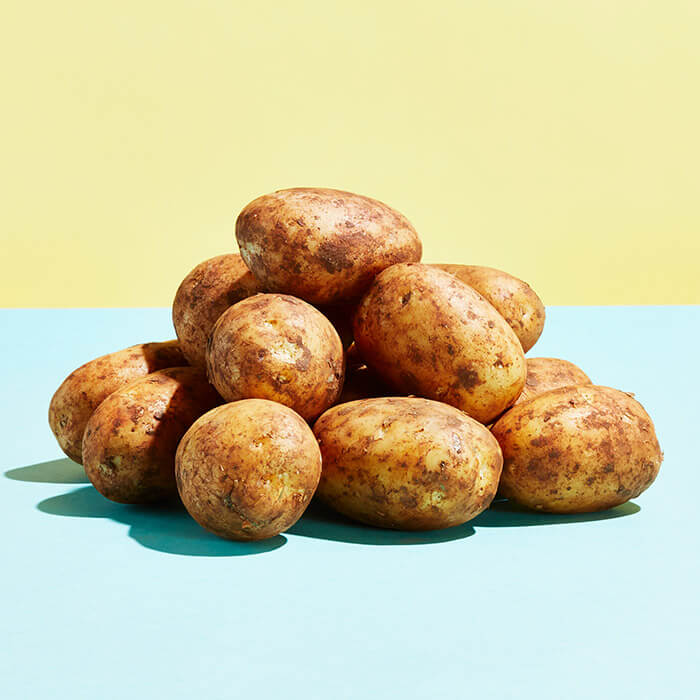 Pile of potatoes on top of light blue surface with light yellow background